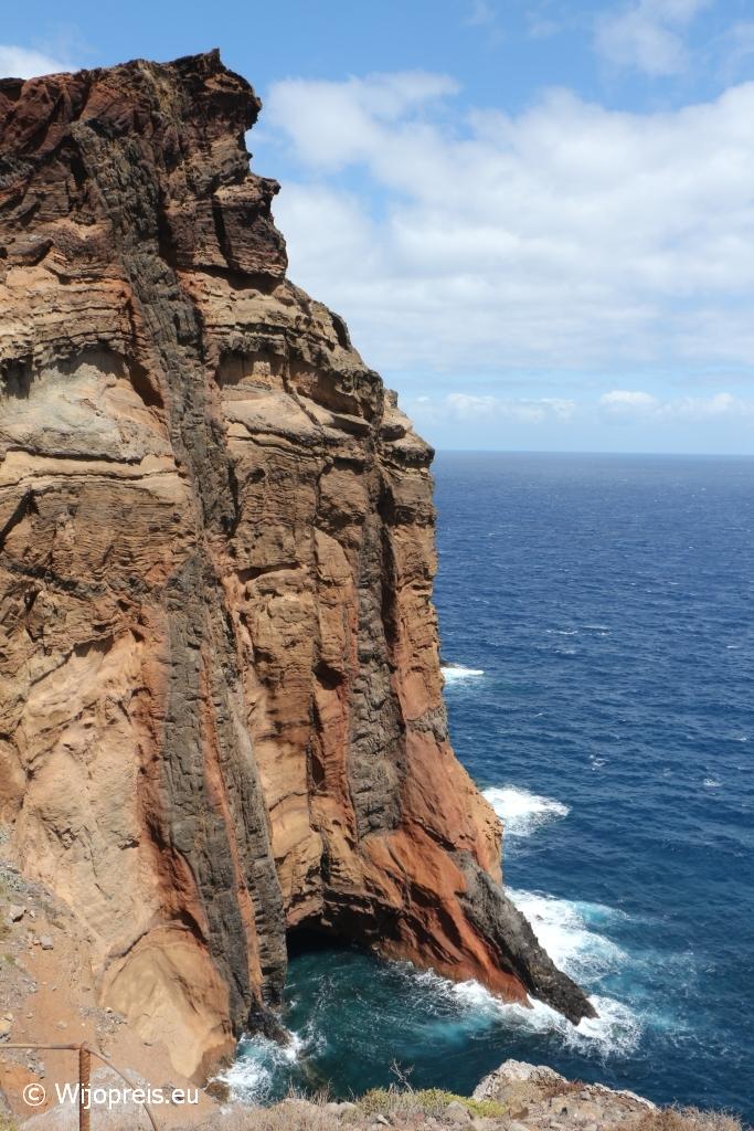 De steile, rode kliffen steken mooi af tegen de knalblauwe zee